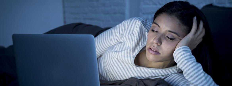 young beautiful hispanic internet addict woman in pajamas on bed